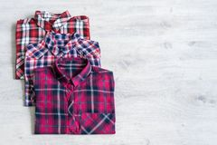 Three multi-colored checkered women`s shirts lying neatly folded royalty free stock photos