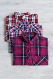 Three multi-colored checkered women`s shirts lying neatly folded stock photos