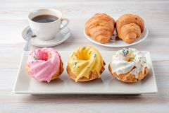 Three multi-colored cupcakes on a rectangular plate. Three multi-colored cupcakes on a rectangular plate, cup of black coffee and plate with two croissants on a Stock Photography