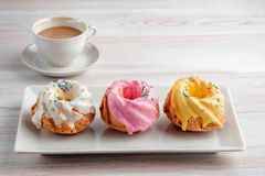 Three multi-colored cupcakes on a rectangular plate. Three multi-colored cupcakes on a rectangular plate and a cup of espresso on a light table texture. Copy Stock Image