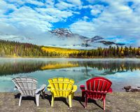 Three multi-colored deck chairs. Rocky Mountains of Canada. Three comfortable multi-colored deck chairs stand by the Piramid lake. Concept of ecological, active stock photo