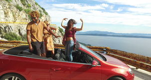 Three multi ethnic friends dancing in convertible parked with sea in background. Three multi ethnic friends dancing in red convertible car parked on the side of stock video