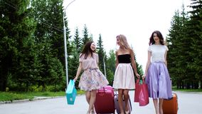 Three multi ethnic girls with suitcases and shopping bags walk on vacation. stock footage