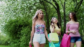 Three multi ethnic happy girls walking with purchases packages after shopping. stock footage
