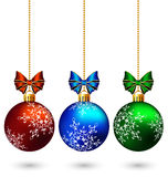 Three multicolored christmas balls with bows isolated on white Stock Photography