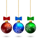 Three multicolored christmas balls with bows isolated on white Stock Photos