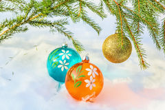 Three multicolored Christmas balls and fir branch Royalty Free Stock Photo