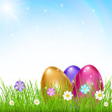 Three multicolored eggs in grass with flowers Stock Photo