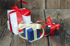 Three multicolored gift boxes with red and yellow ribbons Stock Photos