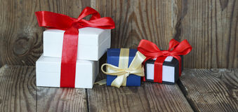 Three multicolored gift boxes with red and yellow ribbons Royalty Free Stock Photos