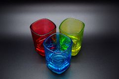 Three multicolored shot glasses on black background stock images