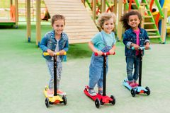 three multicultural adorable little children riding on kick scooters stock images