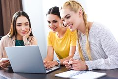 Three multicultural businesswomen using laptop at table in modern. Office stock photo