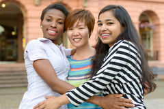 Three multicultural women embracing themselves. Three multicultural cheerful young women embracing themselves Royalty Free Stock Photos