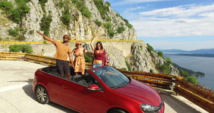 Three multiethnic friends dancing in convertible parked with sea in background. Three multiethnic friends dancing in red convertible car parked on the side of stock footage