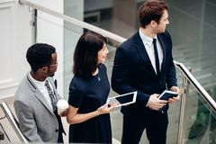 Three multiracial business people walking down on stairs with digital tablet. Team business people wear suit and walking down on step of stair and holding Stock Photos