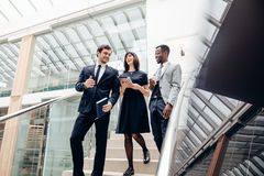 Three multiracial business people walking down on stairs with digital tablet. Three happy multiracial business people walking down on stairs together with Royalty Free Stock Photography