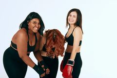 Three multiracial diverse woman in black sportswear posing in boxing gloves royalty free stock photo
