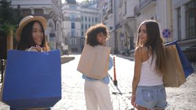 Three multiracial girls with shopping bags smiling