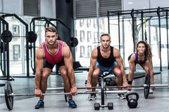 Three muscular athletes lifting a barbell Royalty Free Stock Photography