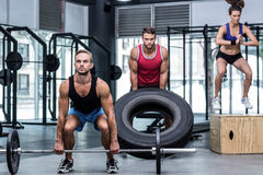 Three muscular athletes lifting and jumping Stock Photo