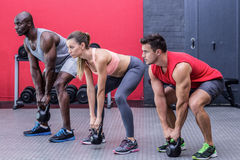 Three muscular athletes squatting together. Side view of three muscular athletes squatting with kettlebells Royalty Free Stock Images