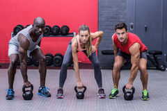 Three muscular athletes about to lift a kettle bell Royalty Free Stock Photos