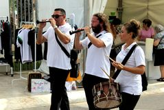 Three musicians playing their instruments at The Farming Fair in Elche city, Alicante, Spain. Elche, Alicante, Spain; on October 13, 2018: Three street stock photo
