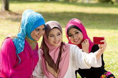 Three muslim girls with cellphone. Three beutiful muslim girls with red cellphone camera Royalty Free Stock Images