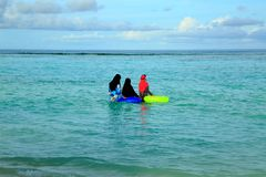 Three muslim women in colorful clothes are standing in water and going swimming. Turquoise water of Indian Ocean, Maldives. Blue sky and white clouds stock photo