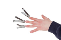 Three nail clippers opposite the fingers of a male hand Stock Image