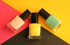 Three nail polish bottles, colorful background. Three different nail polish bottles yellow, mint and neutral on colorful background black, pink and yellow, close stock images