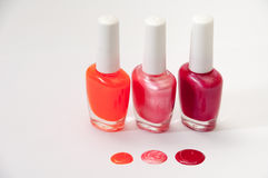 Three nail polish and nail polish spilled on a white background Royalty Free Stock Images