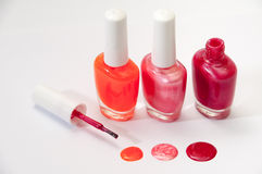 Three nail polish and nail polish spilled on a white background Stock Image