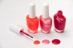Three nail polish and nail polish spilled on a white background Stock Image