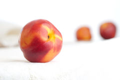 Three Nectarines on Embroidered Napkin Stock Photos