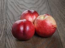 Three nectarines on old wood oak table Stock Image