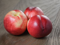 Three nectarines on old wood oak table Stock Images