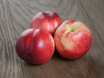 Three nectarines on old wood oak table Royalty Free Stock Photo
