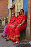 Three Nepalese ladies in red sarees sitting at Swayambhu Temple. The focus of this image is mainly on the second and third ladies. This image is taken at the Stock Photos