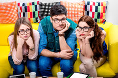 Three nerds on the couch. Three nerds in eyeglasses sitting on the couch and looking at camera Stock Images