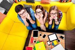 Three nerds on the couch. Three nerds in eyeglasses sitting on the couch and looking at camera with different gadgets on the background Royalty Free Stock Images