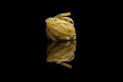 Three nest pasta with quail eggs on black background Stock Photos