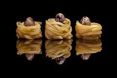 Three nest pasta with quail eggs on black background Stock Photo