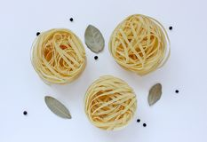 Three nests of pasta, bay leaves and black pepper. On white background royalty free stock image