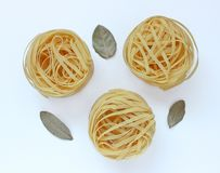 Three nests of pasta and bay leaves. On white background royalty free stock photos