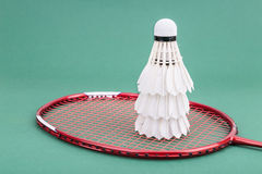 Three new badminton shuttlecock with rackets on green mat court. Three new badminton shuttlecock and rackets on green mat PVC court Royalty Free Stock Image