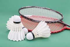 Three new badminton shuttlecock with rackets on green mat court Royalty Free Stock Image