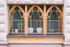 Three new replacement windows with green trim on front of house. Horizontal royalty free stock image