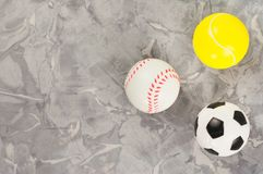 Three new soft rubber soccer and tennis and baseball balls in form of triangle on old worn cement stock photography